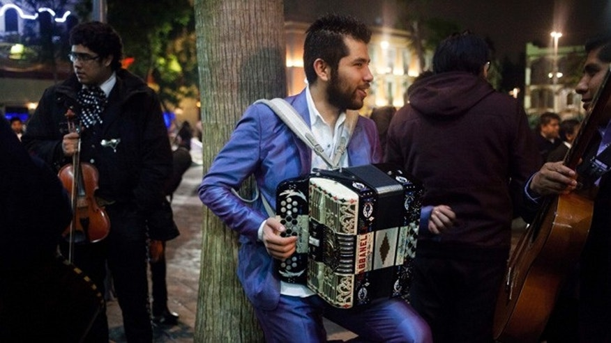 In this Aug. 21, 2015 photo, a norteño musician with his accordion waits for customers in Garibaldi Plaza in Mexico City. Northern Mexican music features the accordion as well as the bajo sexto, a 12 string instrument resembling a guitar. (AP Photo/Sofia Jaramillo)
