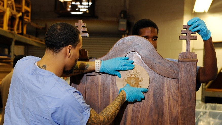 Inmates Evan Davis, left, and Rameen Perrin fix a cross and plaque on a chair carved out of walnut for Pope Francis to use during his planned visit to the prison next month, Monday, Aug. 24, 2015, at the Curran-Fromhold Correctional Facility in Philadelphia. Francis plans to meet on Sept. 27 with about 100 inmates and some of their relatives during a two-day trip to the city. (AP Photo/Michael Perez)