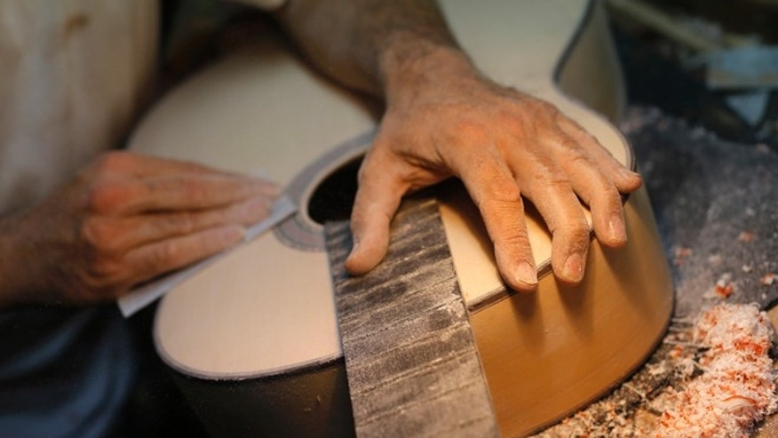 In this Wednesday, Nov. 11, 2015 photo, Spanish guitar maker Mariano Conde works at his workshop in Madrid. Carrying on the family tradition is Mariano Conde, who operates out of his workshop in downtown Madrid where and he and his son, also called Mariano, build their hand-made, individually sounding, classical and flamenco guitars. Spanish flamenco guitars are known for their beautiful shape, rich wood colors and full-bodied, crisp musical tones. (AP Photo/Francisco Seco)