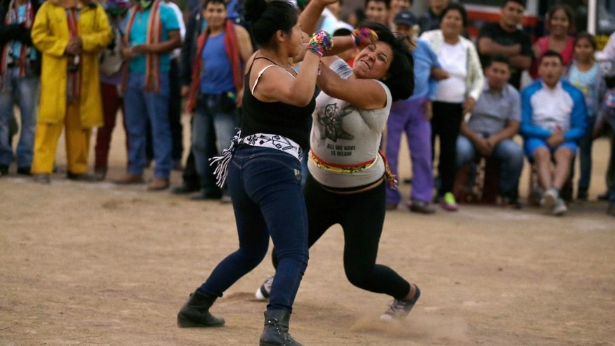 "In this Dec. 25, 2015 photo, Karen Quispe, left, and Margarita Rengifo, who don't know each other, throw punches during the ""Takanakuy"" ritual fighting event on the outskirts of Lima, Peru on Christmas day. Only once a judge has ruled one of the combatants licked do they stop fighting. (AP Photo/Martin Mejia)"