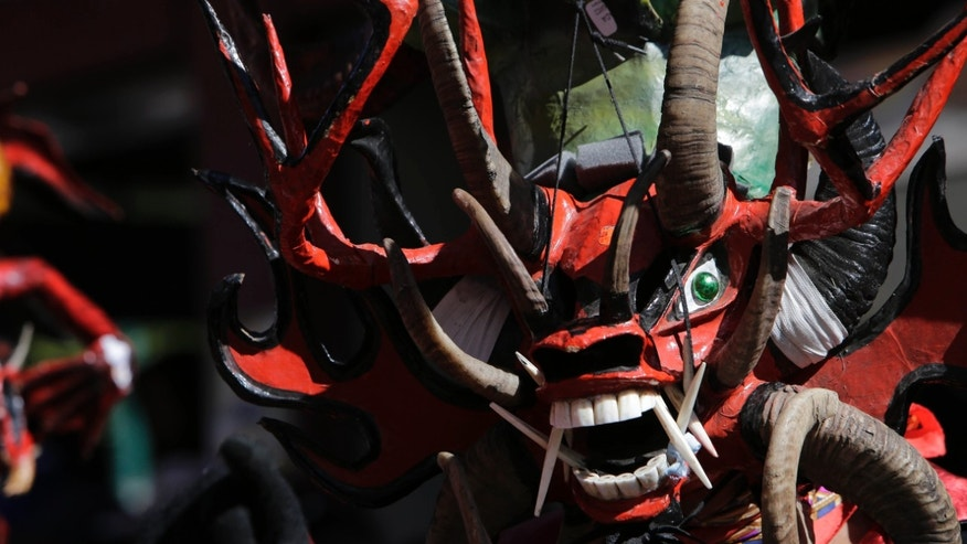 CORRECTS LENGTH OF FESTIVAL FROM EIGHT TO SIX DAYS - A man dressed as a 'devil' dances during the 'Diablada' festival, in Pillaro, Ecuador, Tuesday, Jan. 5, 2016. 'Devils' invade this highlands town just before New Year's and take over its streets for six days, donning fearful masks to dance to the rhythms of local bands. The masks that participants don typically include enormous horns, pointed ears and diabolical smiles. (AP Photo/Dolores Ochoa)