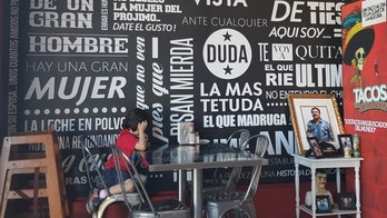 "LOS ANGELES - A young boy sits at a table in Los Tacos Desvelados against one of the taquería's graffiti style walls. To the right is an altar dedicated to Joaquin ""El Chapo"" Guzman."