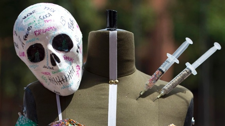 A fake skull and syringes decorate a finished outfit atop a dressmaker's dummy during a student competition to craft fashions inspired by the effects of the drug trade on Mexican culture, at the IberoAmerican University in Mexico City, Wednesday, March 16, 2016. About 200 fashion design and textile students participated in the two-hour competition, building outfits featuring skulls, fake blood and syringes. (AP Photo/Rebecca Blackwell)
