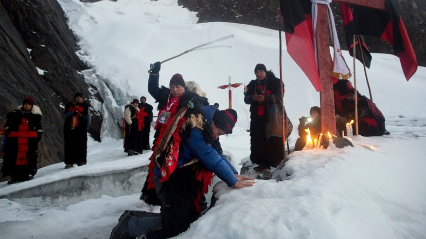"In this May 24, 2016 photo, an ""ukuku"" pledge places his hands on the ice of the Qullqip'unqu mountain glacier, kneeling before a cross as he is whipped three times by an ukukus leader, in an induction ceremony, as part of the syncretic festival Qoyllur Rit'i, translated from the Quechua language as Snow Star, in the Sinakara Valley, in Peru's Cusco region. New recruits promise to make the pilgrimage three years in a row. (AP Photo/Rodrigo Abd)"
