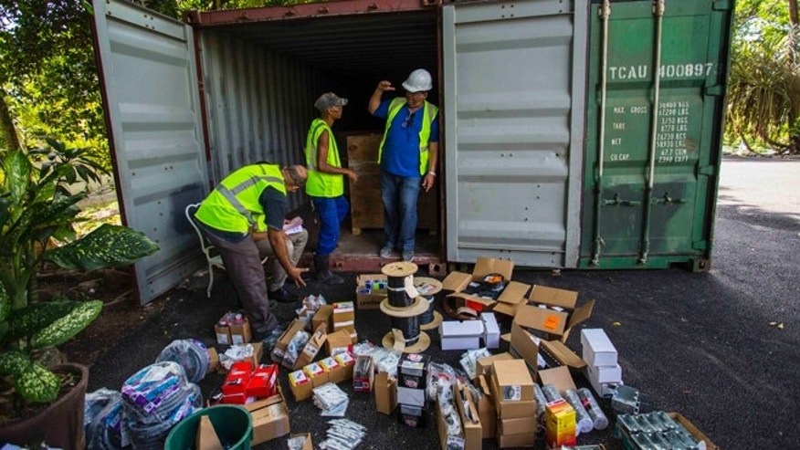 Workers unload a newly arrived container container filled with construction tools and supplies at Finca Vigia, home of U.S. writer Ernest Hemingway in Havana, Cuba, Wednesday, June 15, 2016. The container with box after box of U.S.-bought tools and hardware, from electric fuse boxes to hurricane-proof windows will be used to build a conservation facility for Hemingway artifacts ranging from books and letters to fishing rods and African animal heads. (AP Photo/Desmond Boylan)