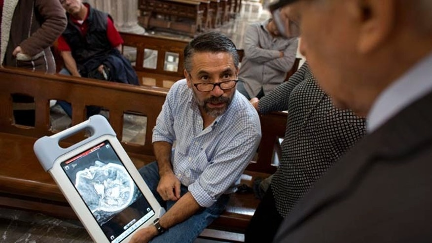 Veterinarian and mobile radiography specialist Jose Luis Velazquez shows a Catholic priest a high-definition x-ray of the molded wax head of Saint Felicitas of Rome, at the Metropolitan Cathedral in Mexico City, Friday, July 8, 2016. Non-invasive imaging technology is giving researchers in Mexico their first glimpse at the interiors of centuries-old life-size religious reliquaries representing Catholic saints. X-rays revealed what appeared to be bone fragments inside Saint Felicitas' wax head.(AP Photo/Rebecca Blackwell)
