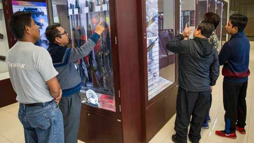 In this July 15, 2016 photo, customers look over guns available for purchase at the country's lone gun store in Mexico City. Those who enter must surrender any cellphones, tablets or cameras, remove caps and pass through a metal detector. (AP Photo/Nick Wagner)