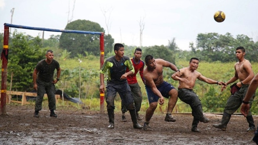 In this Aug. 11, 2016 photo, rebels of the 48th Front of the Revolutionary Armed Forces of Colombia play soccer at their camp in the southern jungles of Putumayo, Colombia. The guerrillas, behaving like laid-back, sport-loving youths, are taking security risks that would've been unthinkable just months ago. (AP Photo/Fernando Vergara)