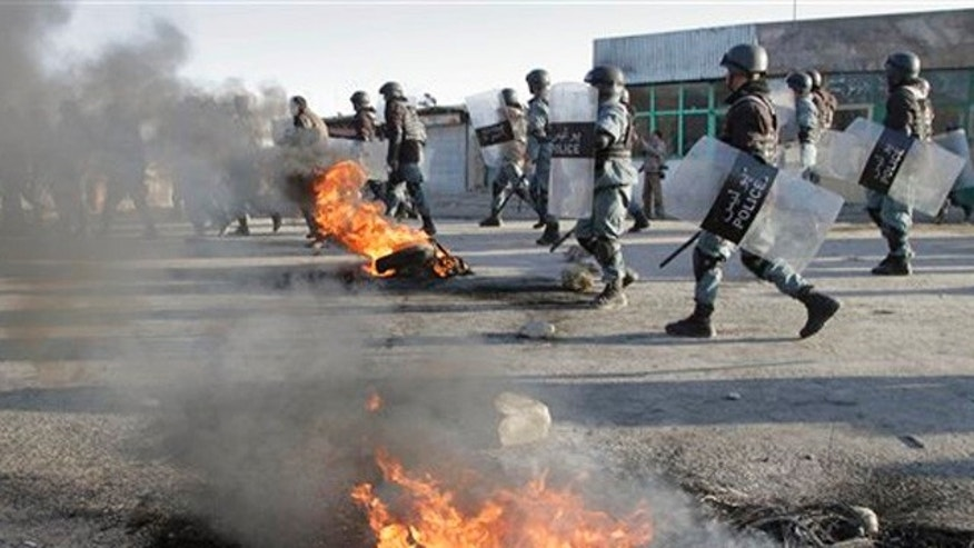 Feb. 24, 2012: Afghan policemen walk past burning tires during an anti-U.S. demonstration in Kabul, Afghanistan.