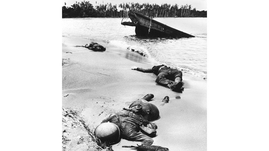 Three dead Americans lie on the beach at Buna.