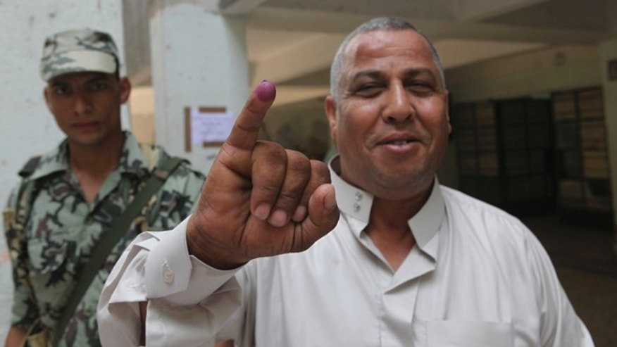 June 16, 2012: An Egyptian voter displays his ink-stained finger, proving he cast his ballot, in a polling station in Cairo, Egypt.