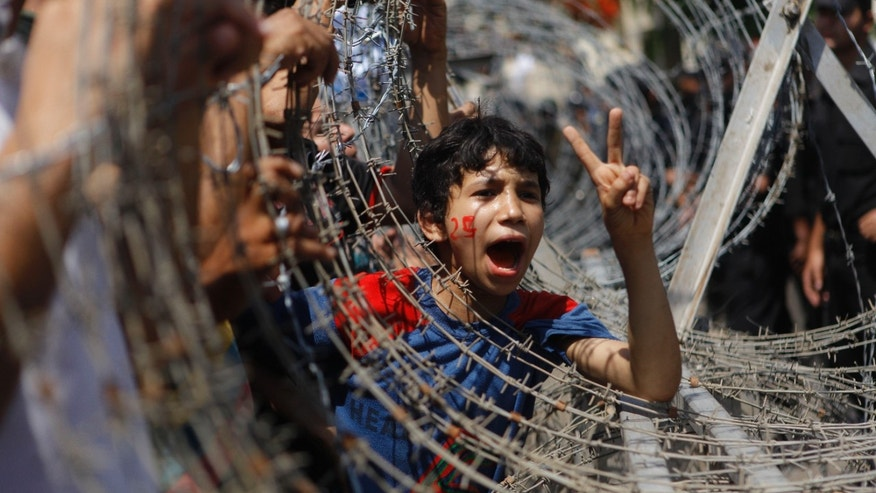 An Egyptian boy peers out of barbed wire, his face painted with the number 25, the date of the Egyptian revolution, during a protest in front of the Supreme Constitutional Court in Cairo, Egypt, Thursday June 14, 2012. Egypt's highest court has ruled that Hosni Mubarak's last prime minister can stay in the presidential race. (AP Photo/Amr Nabil)