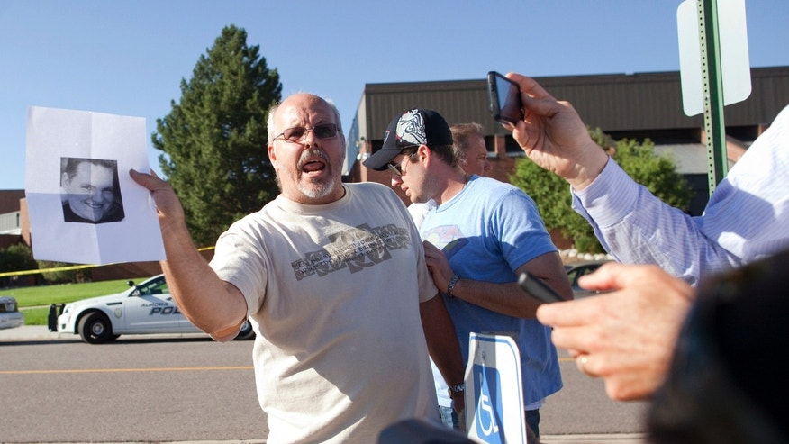 July 20, 2012: Tom Sullivan , holds a photograph of his son, Alex Sullivan, as he pleads with the media to help him find his son, outside Gateway High School on Friday in Aurora, Colo.  Alex Sullivan, was celebrating his 27th birthday by attending midnight premiere of the Batman movie Friday night.