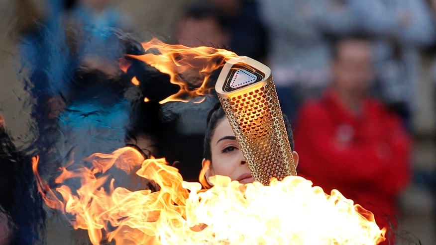 Actress Ino Menegaki, dressed as a high priestess, lights the torch at a ceremony in Panathinean stadium in Athens, Thursday, May 17, 2012. The torch begins its 70-day journey to arrive at the opening ceremony of the London 2012 Olympics, from the Greek capital, to cover about 8,000-mile (12,875-kilometer) on its progress over many parts of England to start the games. (AP Photo/Petros Giannakouris)