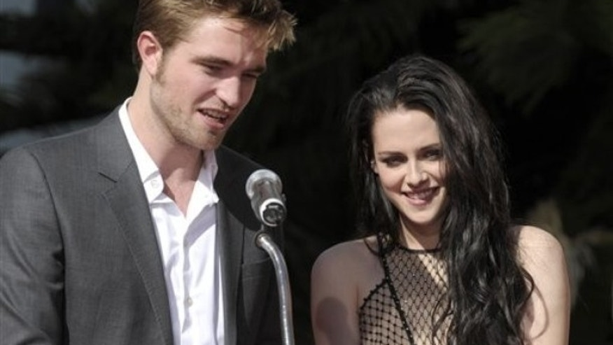 Actor Robert Pattinson, left, and actress Kristen Stewart speak at their Twilight hand and footprint ceremony at The Chinese Theatre in Los Angeles on Thursday, Nov. 3, 2011. (AP Photo/Dan Steinberg)