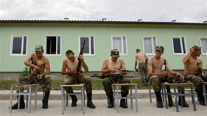 Russian soldiers clean their rifles at the military base in Tskhinvali, regional capital of Georgia's breakaway province of South Ossetia, Friday, Aug. 7, 2009. The separatist Georgian region marks the anniversary of the Georgian invasion that resulted in a brief Russia-Georgia war in Aug. 2008. (AP Photo/Sergey Ponomarev)
