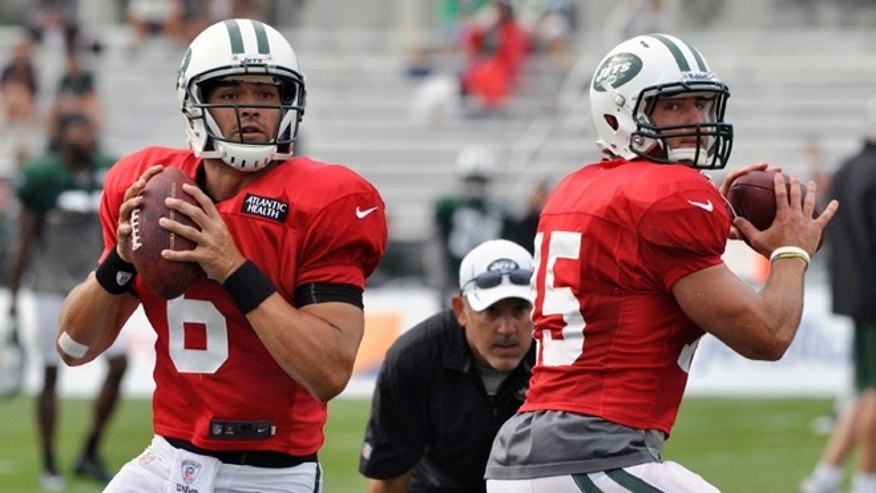 ADVANCE FOR WEEKEND EDITIONS, AUG. 25-26 - This Aug. 14, 2012 file photo shows Mark Sanchez, left, and Tim Tebow set to throw during drills at New York Jets training camp in Cortland, N.Y.  Two-quarterback systems have rarely worked, but the Jets plan to test that theory with Sanchez and Tebow this season. (AP Photo/Kevin Rivoli, File)