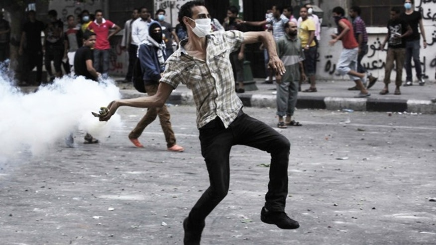 Sept. 13, 2012: An Egyptian protester throws back a tear gas canister toward riot police, unseen, outside the U.S. embassy in Cairo, Egypt.