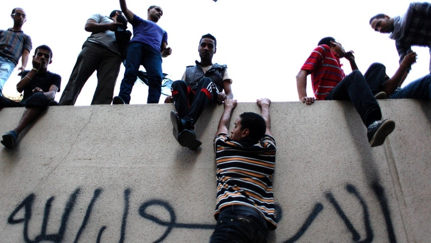 "Sept. 11, 2012: Egyptian protesters climb the walls of the U.S. embassy with Arabic graffiti that reads ""any one but you God's prophet"" during a protest in Cairo, Egypt."