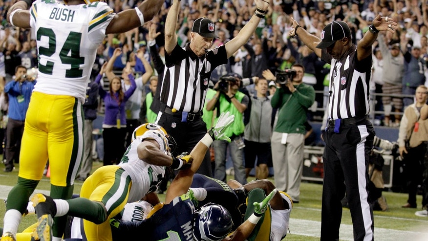 Sept. 24, 2012: Officials signal a touchdown by Seattle Seahawks wide receiver Golden Tate, obscured, on the last play of an NFL football game against the Green Bay Packers.