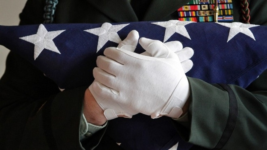 A National Guard captain holds a folded American flag.
