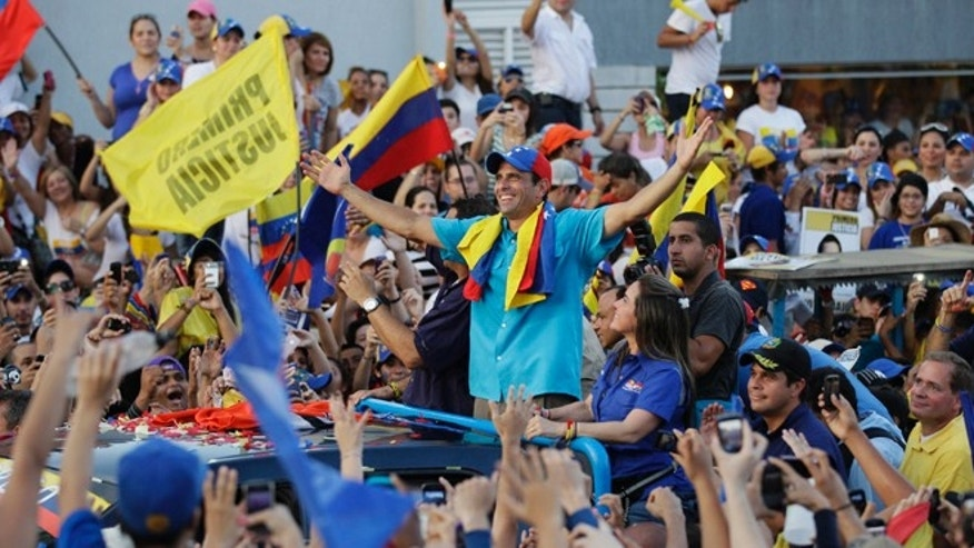 Oct. 3, 2012: Opposition presidential candidate Henrique Capriles gestures from the top of a vehicle during a campaign rally in Maracaibo, Venezuela.