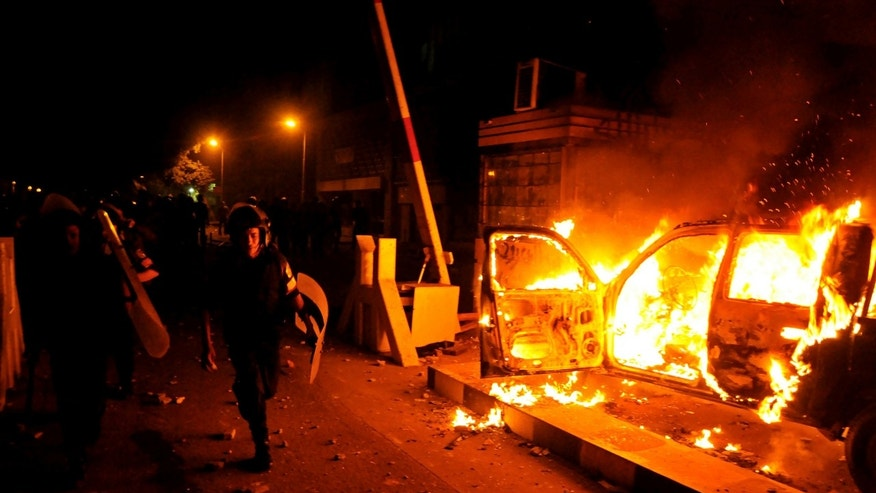 A riot policeman passes burning vehicles during clashes outside the U.S. embassy in Cairo, Egypt, early Thursday, Sept. 13, 2012, as part of widespread anger across the Muslim world about a film ridiculing Islam's Prophet Muhammad. (AP Photo/Hussein Tallal)