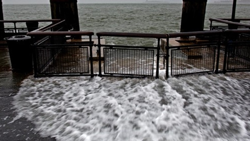 Waves wash over the sea wall near high tide at Battery Park in New York, Monday, Oct. 29, 2012 as Hurricane Sandy approaches the East Coast. Hurricane Sandy continued on its path Monday, forcing the shutdown of mass transit, schools and financial markets, sending coastal residents fleeing, and threatening a dangerous mix of high winds and soaking rain. (AP Photo/Craig Ruttle)