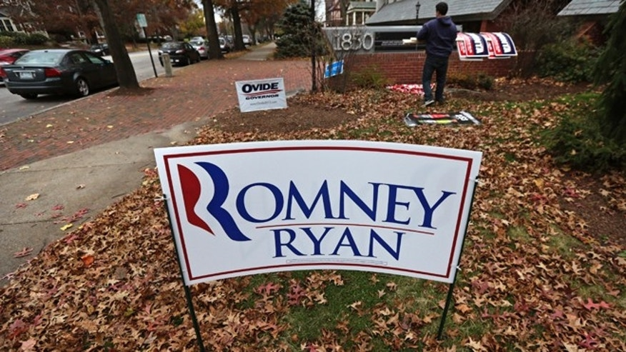Nov. 7, 2012: A campaign worker removes candidate signs from in front of Mitt Romney's campaign office in Manchester, N.H.