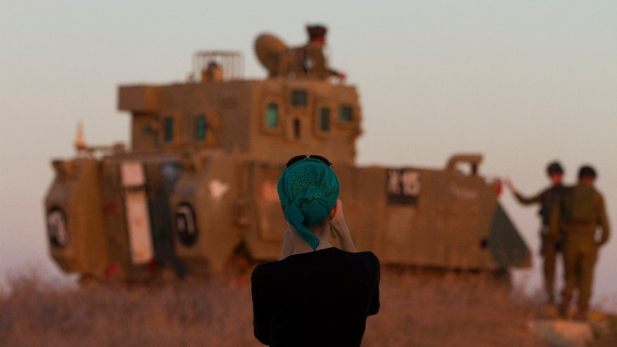 "A woman photographs Israeli soldiers on top an armored personel carrier close to the Israel Gaza Border, southern Israel,Thursday, Nov. 15, 2012. Israel's prime minister says the army is prepared for a ""significant widening"" of its operation in the Gaza Strip. Benjamin Netanyahu told reporters on Thursday that Israel has ""made it clear"" it won't tolerate continued rocket fire on its civilians. (AP Photo/Ariel Schalit)"