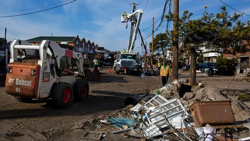 Nov.12, 2012: A crew with Salt River Project of Arizona (SRP) works on replacing a pole on a sand and debris-covered street in the Belle Harbor neighborhood of the borough of Queens, New York in the wake of Superstorm Sandy.