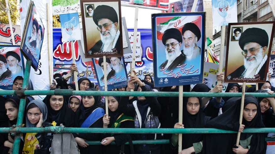 Nov. 2, 2012: Holding posters of the late revolutionary founder Ayatollah Khomeini, and Supreme Leader Ayatollah Ali Khamenei, Iranian girls attend an annual state-backed rally in front of the former US Embassy in Tehran, Iran. The rally marks the Nov. 4, 1979, storming of the building by militant students who held 52 Americans hostage for 444 days to protest U.S. failure to hand over the toppled shah Mohammad Reza Pahlavi to Iran for trial.