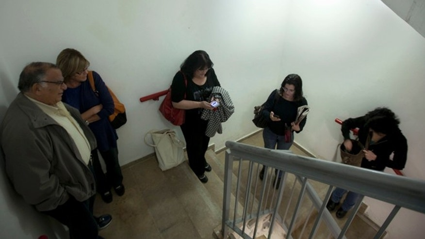 Nov. 16, 2012: Israelis take cover inside a staircase during a siren alerting from a rocket thought to have been fired by Palestinian militants from the Gaza Strip, at a hospital in Jerusalem.