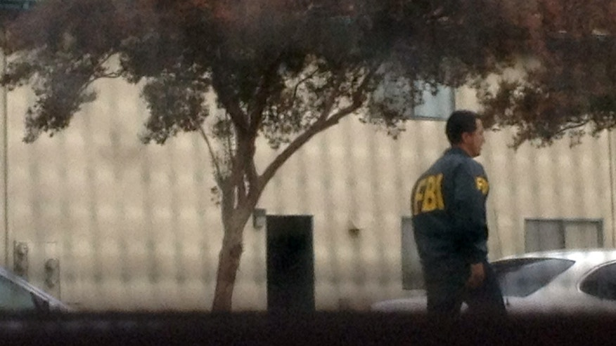 Law enforcement and FBI agents during a raid at the home of 21-year-old Miguel Alejandro Santana Vidriales of Upland, Calif, on Friday, Nov. 16, 2012.