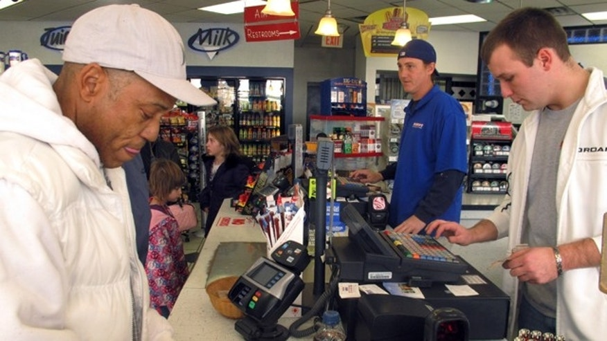 Nov. 23, 2012: Michael Arrington, left, buys a Powerball ticket from cashier Lee Heilig, right, at a DeliMart convenience store in Iowa City, Iowa.