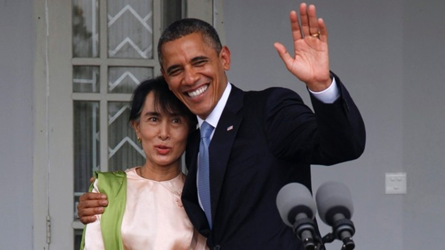 Nov. 19, 2012: U.S. President Barack Obama waves to the media as he embraces Burma opposition leader Aung San Suu Kyi at her residence in Yangon, Burma.