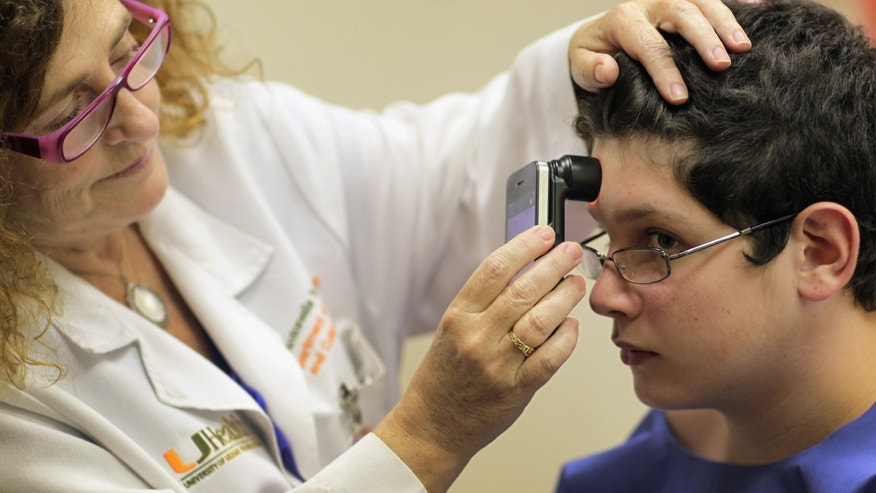 "MIAMI, FL - JUNE 15:  Doctor Antonella Tosti, Dermatologist University of Miami School of Medicine, uses an iphone as a dermatoscope as she examines Michael Casa Nova,12, for symptoms of skin cancer due to sun exposure on June 15, 2011 in Miami, Florida. The federal Food and Drug Administration announced that sunscreen manufacturers are to change the labels on their products to prohibit the use of certain marketing terms. The new rules are meant to help clear up confusion about the meaning of ""sun protection factor,"" or SPF, and other terms like ""waterproof.""  (Photo by Joe Raedle/Getty Images)"