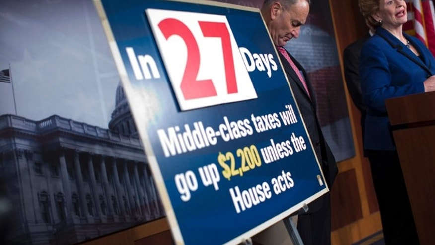 Dec. 5, 2012: Sen. Charles Schumer, D-N.Y. listens at left, next to a fiscal cliff sign, as Sen. Debbie Stabenow, D-Mich., speaks during a news conference on Capitol Hill.