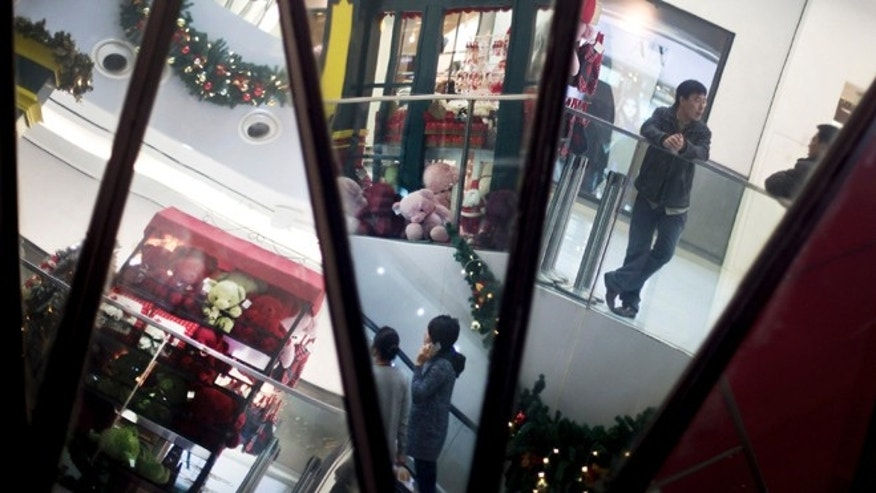 Dec. 10, 2012: Chinese shoppers and Christmas decorations are reflected in mirrors inside a shopping mall in Beijing.