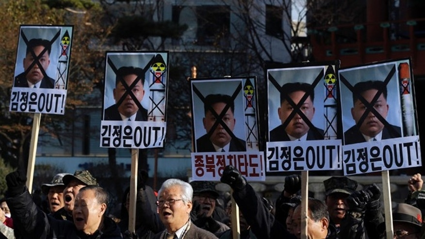 "Dec. 12, 2012.: South Korean protesters shout slogans as they hold the pictures of North Korean leader Kim Jong Un with letters reading ""Out Kim Jong Un"" during a rally denouncing North Korea's rocket launch."