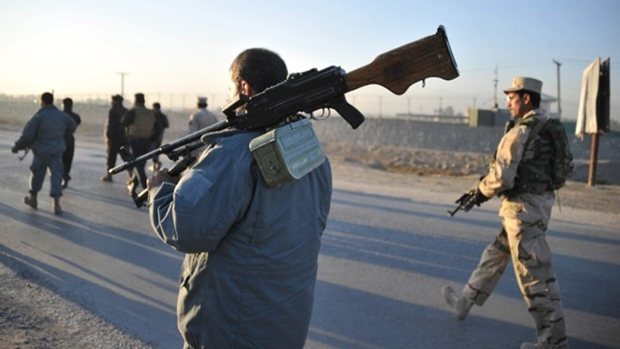 Dec. 2, 2012: Afghan security forces patrol the site where Taliban suicide bombers attacked a joint U.S.-Afghan air base in Jalalabad, east of Kabul, Afghanistan.