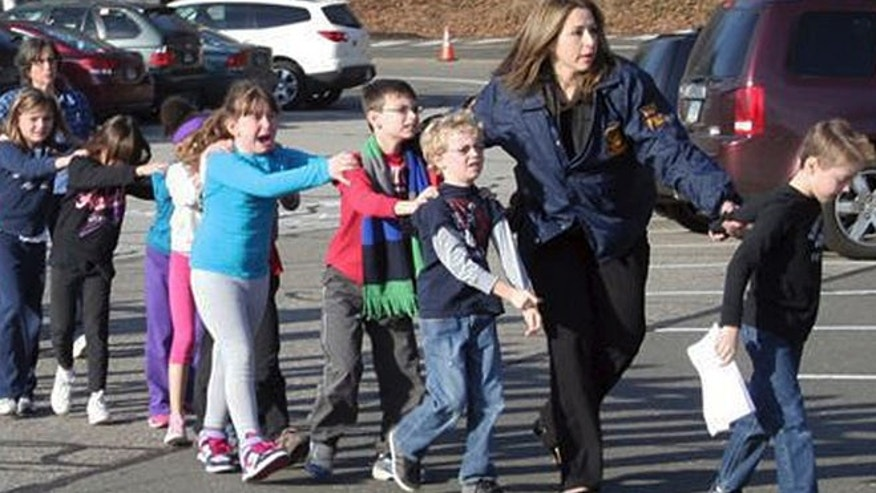 Dec. 14, 2012: In this photo provided by the Newtown Bee, Connecticut State Police lead children from the Sandy Hook Elementary School in Newtown, Conn., following a reported shooting there.