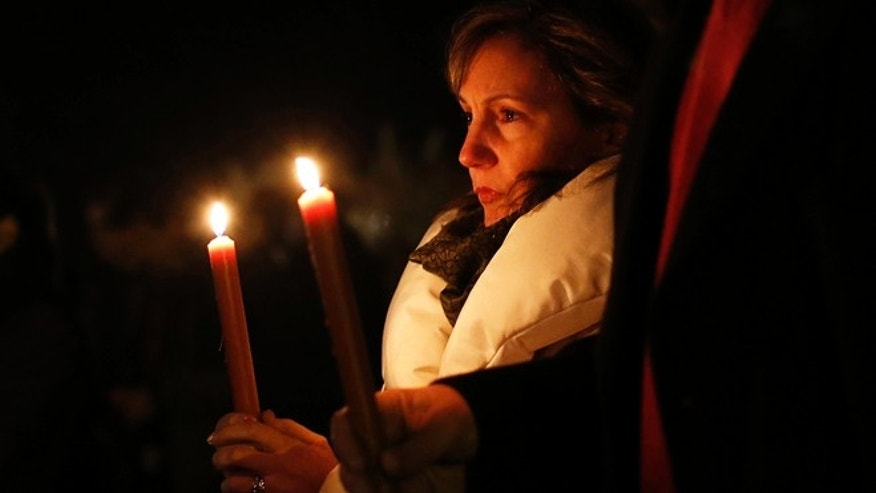 Dec. 14, 2012: People stand with candles outside the overflow area of a vigil at the Saint Rose of Lima church in Newtown, Conn.