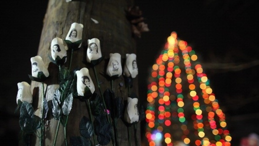White roses honoring children killed at Sandy Hook Elementary School hang at a memorial in Newtown, Connecticut.