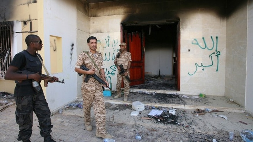 Sept. 14, 2012: Libyan military guards check one of the burnt out buildings at the U.S. Consulate in Benghazi, Libya, during a visit by Libyan President Mohammed el-Megarif to express sympathy for the death of American ambassador to Libya Chris Stevens and his colleagues in the Sept. 11, 2012 attack on the consulate.