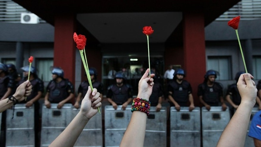Dec. 10, 2012: Activists hold up flowers in front of police officers during a demonstration marking the International Human Rights Day in Asuncion, Paraguay.