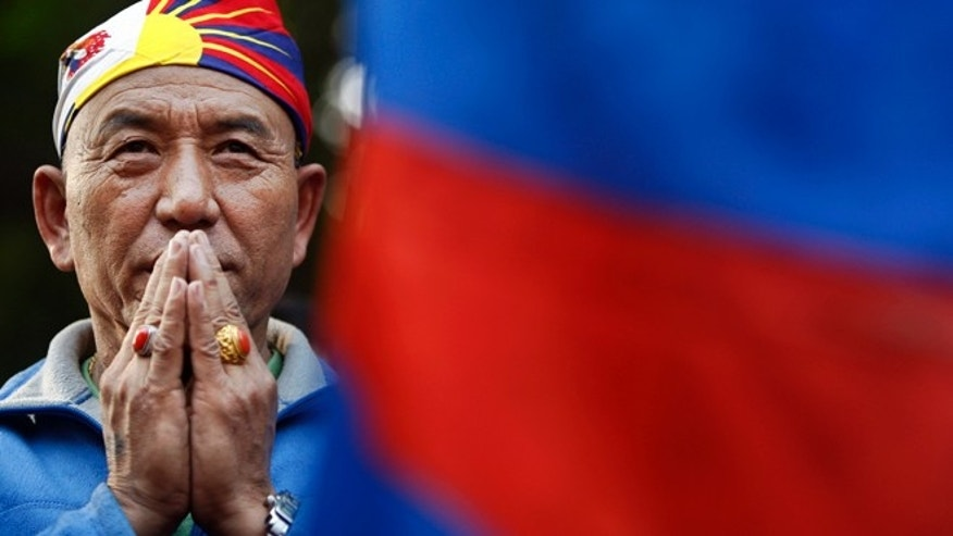 Dec. 10, 2012: An exiled Tibetan Buddhist man prays during a rally to mark World Human Rights Day in New Delhi.