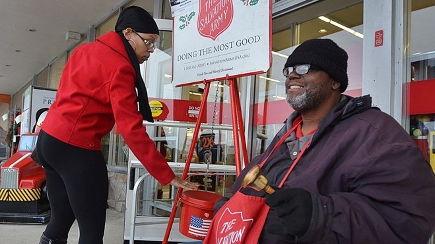 Dec. 7 2012: Vonetta Hudgins puts money in the kettle as Troy Dorn rings the bell for donations for the Salvation Army in front of the Kmart in Pleasantville, NJ.