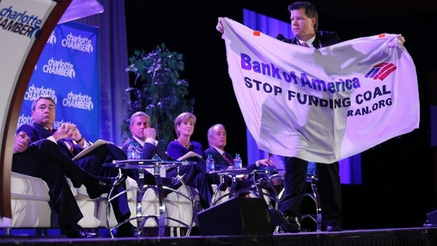 Dec. 17, 2012: A protester carries a banner as he walks across the stage during the Charlotte Chamber's 11th Annual Economic Outlook Conference.