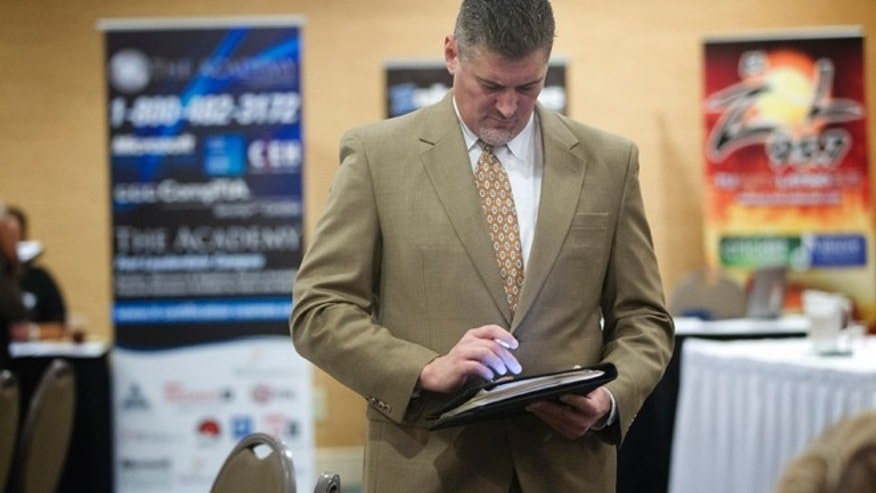 Nov. 30, 2012: An unidentified job seeker uses his iPad to help fill out job applications at the Fort Lauderdale Career Fair, in Dania Beach, Fla.